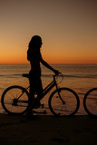 Silhouette of woman on his bike on the beach