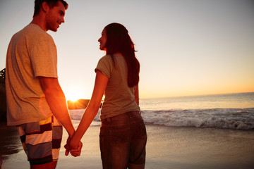 Couple smiling and walking hand in hand on the beach