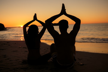 Silhouettes of people practicing yoga sat on the beach