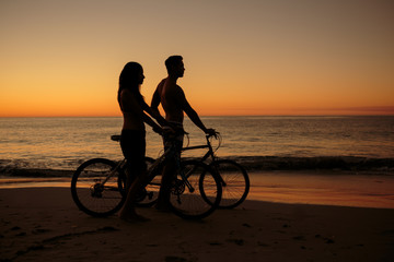 Couple biking together on the beach