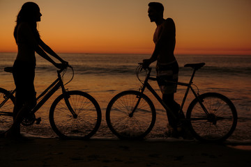 Silhouettes of people on bicycles on the beach