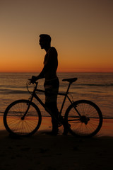 Silhouette of man on his bike on the beach