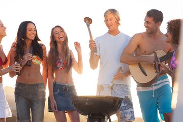 Happy friends preparing barbecue on the beach