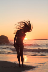 Woman standing on the beach tossing her hair