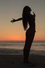 Silhouette of an attractive woman spreading her arms on the beach