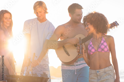 Handsome man playing guitar on the beach