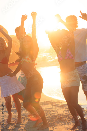 Happy friends raising arms on the beach