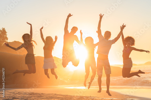 Young people jumping in front of the sunset