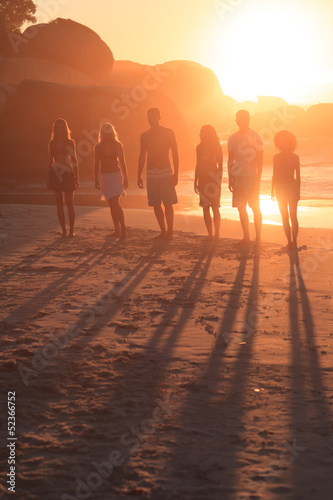 People standing in row in front of the sunset