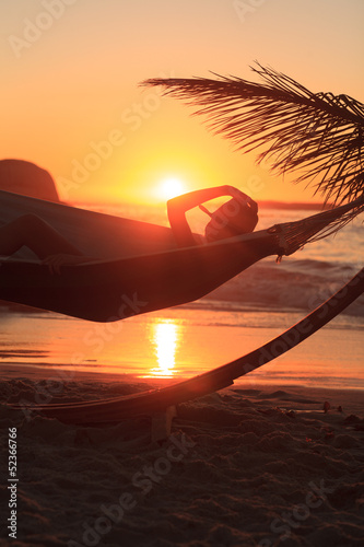 A person wearing a straw hat and relaxing in hammock on the beach