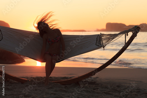 Woman in hammock on the beach shaking her hair