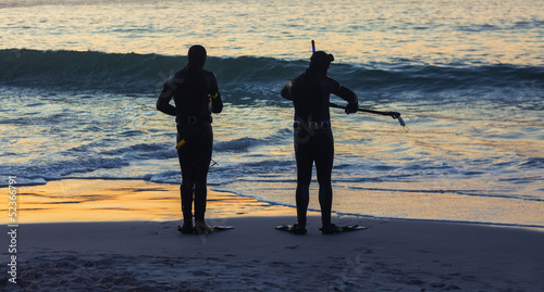 SIlhouettes of people holding snorkeling equipment