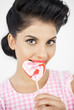 Seductive young pinup biting a lollipop