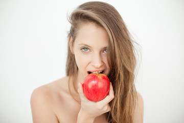 Pretty topless young woman eating a red apple