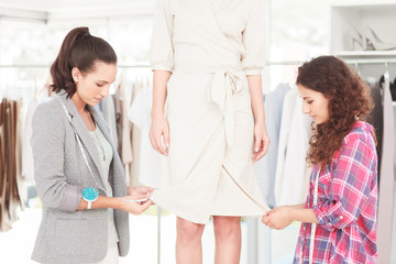 Fashion female designers adjusting a dress