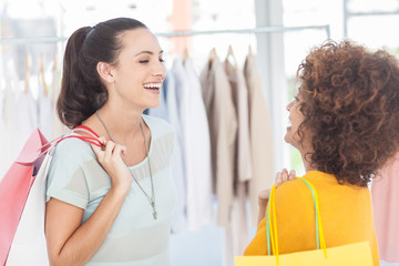 Two attractive friends laughing in a clothing store