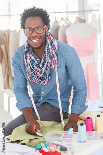 Smiling fashion designer working on a green textile