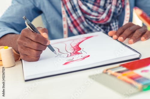 Artistic man drawing clothes in his studio