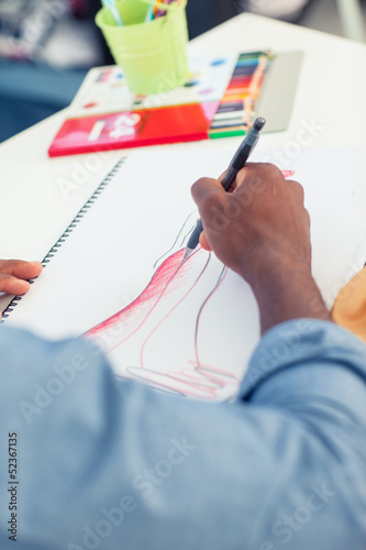 Artistic man drawing clothes in a studio