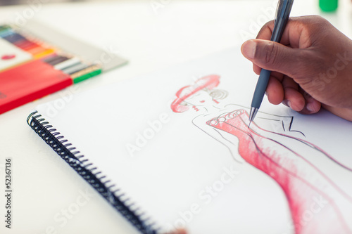 Man drawing clothes with a pencil