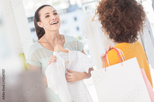 Woman showing her new dress to her friend