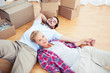 Woman lying on her boyfriend on the wooden floor