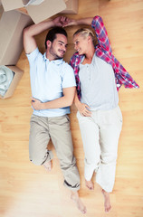 Young lovers lying on the wooden floor