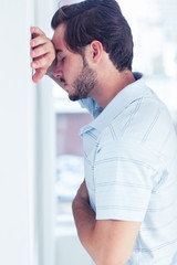 Stressed man leaning against a wall
