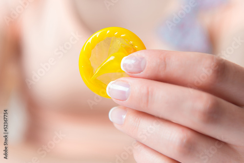 Woman holding condom in hand
