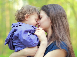 Happy love mother and child girl embracing outdoor summer backgr