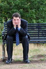 Worried Businessman Sitting On Park Bench