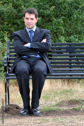 Businessman On Park Bench With Arms Crossed