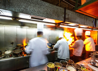 Chef in restaurant kitchen ,doing flambe on food