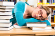 student in library asleep over books
