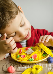 Child playing with spaghetti dish made with plasticine