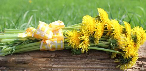Dandelions bouquet lying on a wooden board