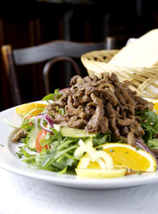 Marinated beef strips on top of a green mixed salad.