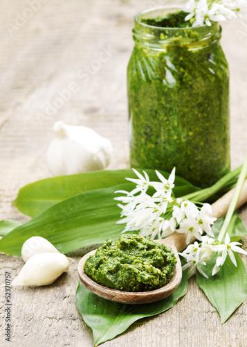 Leinwanddruck Bild Bärlauch-Pesto mit Bärlauchblättern und Bärlauchblüten, Textraum, Copy space, Hochformat