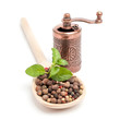 peppercorns on a wooden spoon with grinder