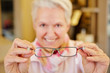 Seniorin hält Brille beim Optiker