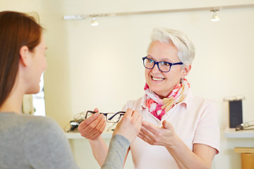 Optiker bietet Frau Brille an