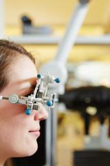 Junge Frau mit Messbrille beim Optiker