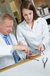 Optiker hilft Azubi bei Reparatur