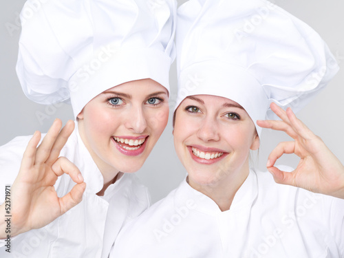 Leinwanddruck Bild Two female apprentices for cooking show thumb up