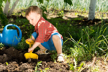 Little boy digging with a toy spade