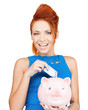 woman putting cash money into piggy bank