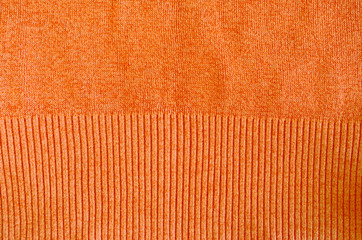 orange knitted wool sweater closeup background