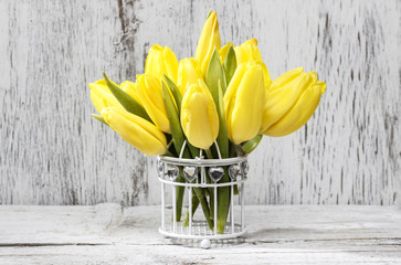 Small bouquet of yellow tulips on white wooden background