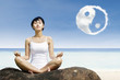 Asian woman meditate under yin yang cloud