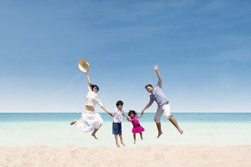 Happy family jumping at beach